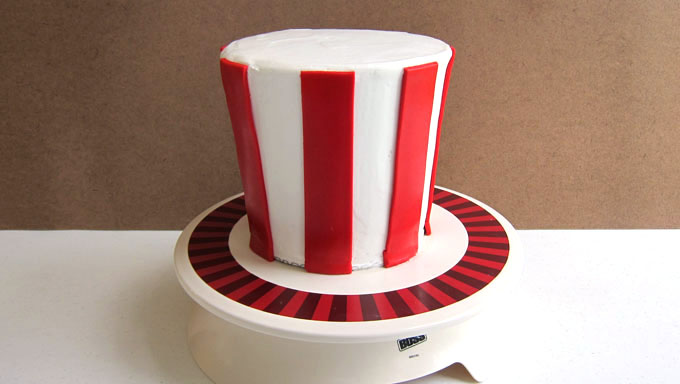 place the red fondant strips around the Uncle Sam Hat cake