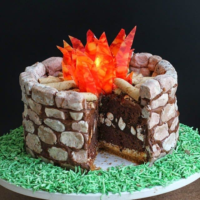Bring the great outdoors inside by building a Campfire S'mores Cake. This decadently rich chocolate cake is made of layers of brownie, toasted marshmallow, graham crackers, chocolate marshmallow ganache, and chocolate marshmallow frosting. Then it's covered in cookies 'n cream fudge rocks and decorated with hard candy flames.