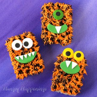 rice krispie treat monsters decorated with orange and black frosting, candy eyes, and modeling chocolate