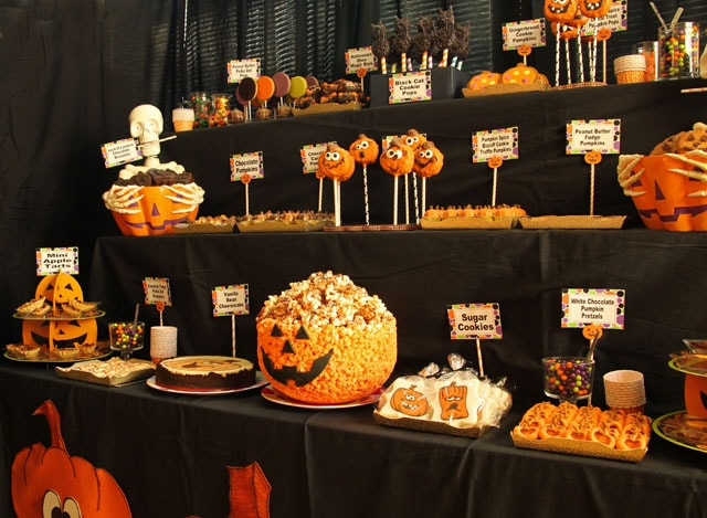 pumpkin party desserts displayed on a three tiered table