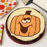 Halloween cheesecake with a chocolate crust is decorated with a naturally colored smiling jack-o-lantern.