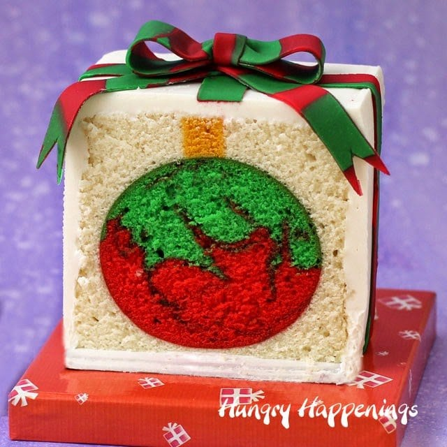 Surprise your loved ones by cutting into a Christmas Present Cake to reveal a red and green swirled ornament hiding inside. This cake will keep people guessing as to what will be inside your next cake!