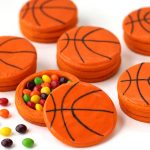 Basketball pinata cookies filled with Skittles are decorated with orange candy melts.