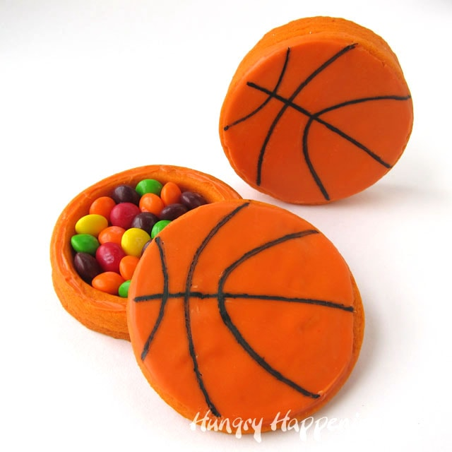 basketball cookies decorated with orange candy melts have candy hiding inside