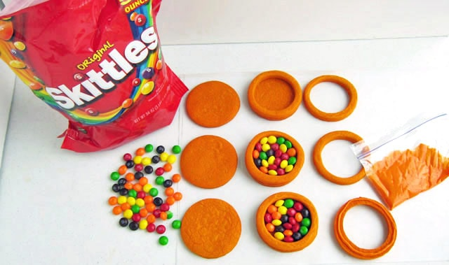 fill round cookies with skittles to create basketball pinata cookies