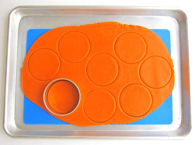 cutting out circles from orange cookie dough to make basketball cookies