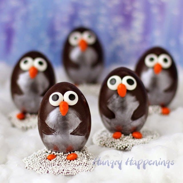 Chocolate Penguin Truffles with White Chocolate Amaretto Raisin Ganache decorated two ways. This version is decorated using luster dust, candy eyes, and candy coated sunflower seeds. https://hungryhappenings.com/