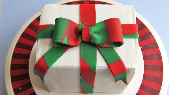 Wrap the cake with the red and green ribbon then attach the fondant bow in the center on top.