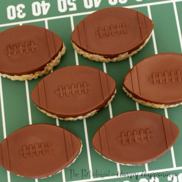 It's wouldn't be a Super Bowl party without them. Hi, it's Kim, The Partiologist back with another game day favorite. I don't think I've ever been to a super bowl party with out seeing a rice krispie treat and these Chocolate Topped Rice Krispie Treat Footballs are so simple and impressive! You can have them ready before kick off!