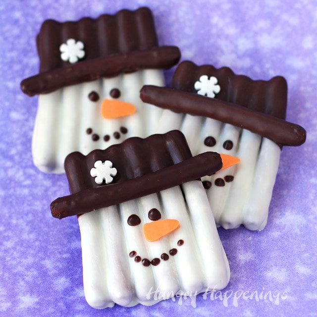 This winter, get crafty in the kitchen by making some sweet and salty snowmen pretzels. Each Chocolate Pretzel Snowman Craft couldn't be cuter with their orange carrot noses and snowflake topped hats. They make perfect Christmas treats and wintertime snacks.