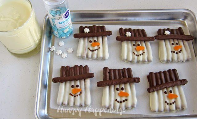 How to make chocolate dipped pretzel snowmen. See the recipe and instructions at HungryHappenings.com.