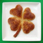 4 leaf clover breakfast sausage pizza on a white platter with a green background