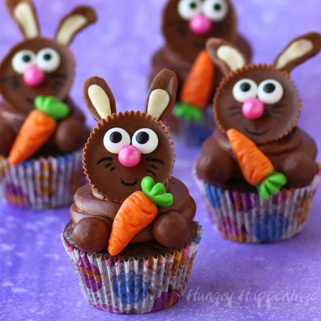 four cute Easter bunny cupcakes made using Reese's Peanut Butter Cups Bunnies each holding a gummy carrot are baked in Easter egg cupcake wrappers