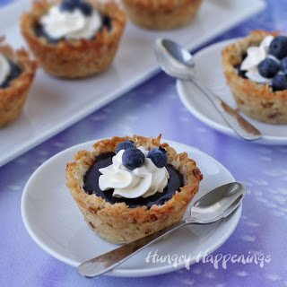 Beautiful coconut macaroon cookie cups filled with homemade blueberry curd make a lovely dessert for Mother's Day.