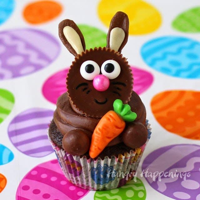 Reese's Cup Easter Bunny Cupcake set on a brightly colored Easter egg paper background