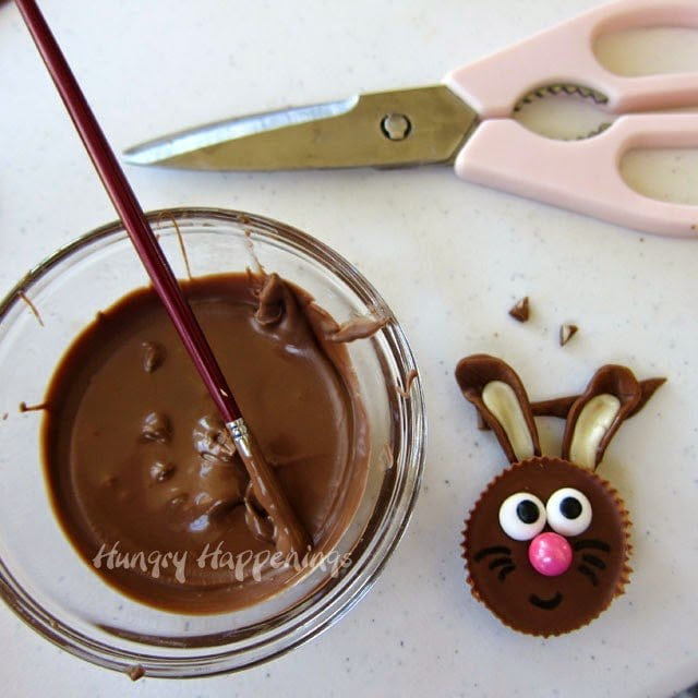 Attach the Tootsie Roll bunny ears to the Reese's Cup using candy melts.
