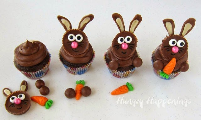 assemble the bunny cupcakes by adding one Reese's Cup Easter bunny on top of a chocolate frosted cupcake then adding two Whoppers for the bunny's front paws and placing a gummy carrot in between so the bunny looks like he's eating or holding the carrot
