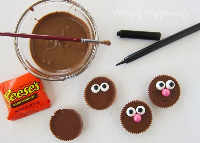 How to make Reese's Cup Easter Bunny Cupcakes using candy melts to attach two candy eyes and a pink Sixlets nose to the peanut butter cup.