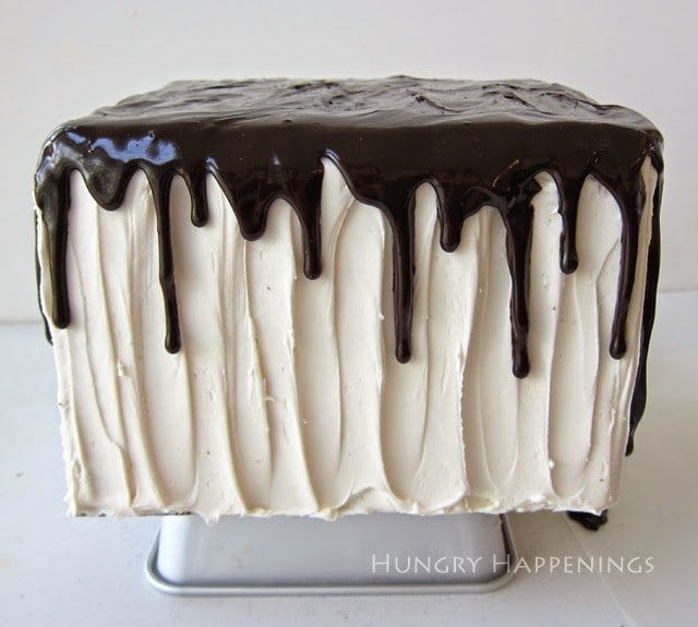 Dripping chocolate glaze over frosted white cake.