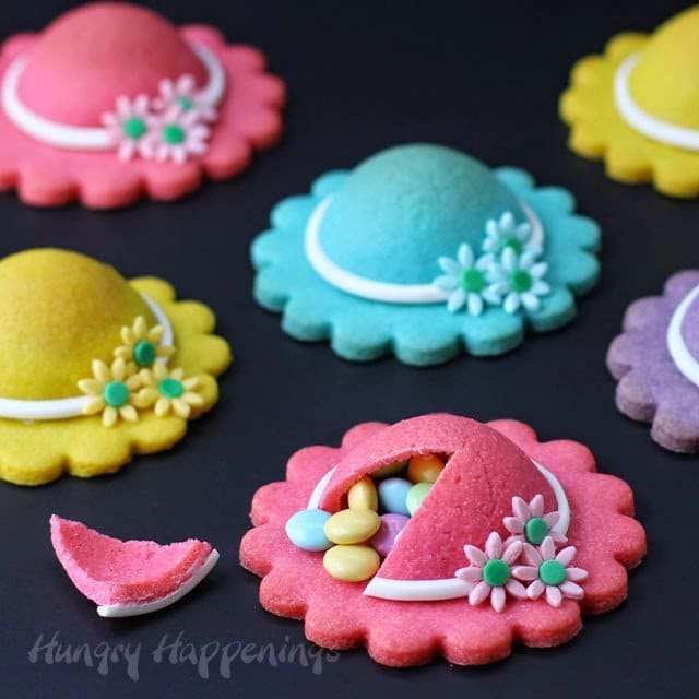 Brightly colored cookies shaped like ladies hats are decorated with modeling chocolate daisies and are filled with pastel colored M&M candies.