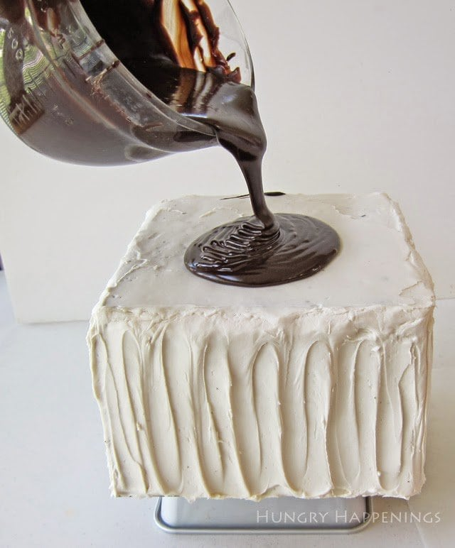 Pouring chocolate ganache over top of cake.