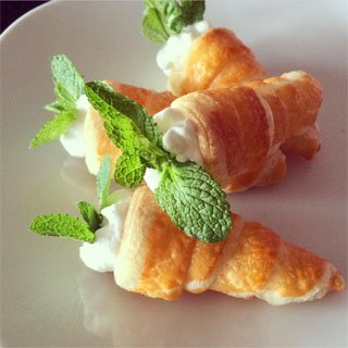 Cream horn carrots made with crescent rolls are filled with fresh whipped cream and mint leaves.