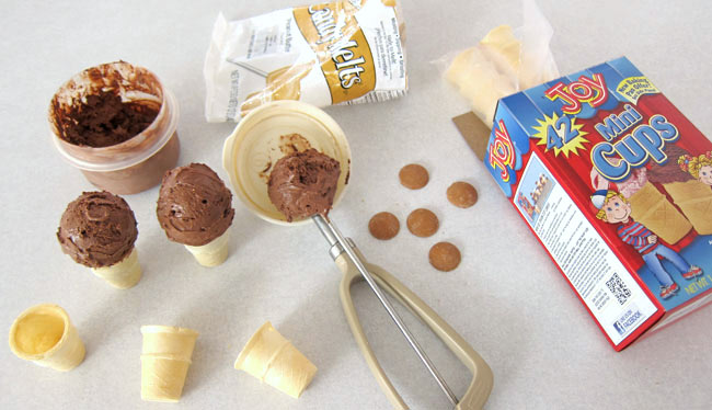 ingredients for monkey ice cream cones including chocolate ice cream, mini cake cones, candy eyes, and peanut butter candy melts