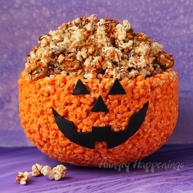 White chocolate popcorn bowl decorated like a jack-o-lantern for Halloween.