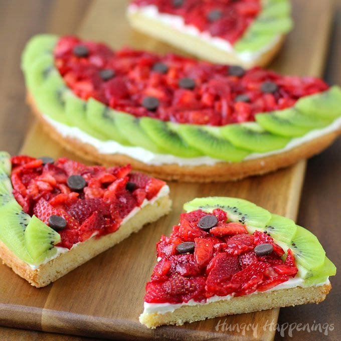 Wow your friends with this fun and festive Strawberry Kiwi Fruit Pizza Watermelon. It looks like a watermelon but tastes like dessert. Recipe from HungryHappenings.com