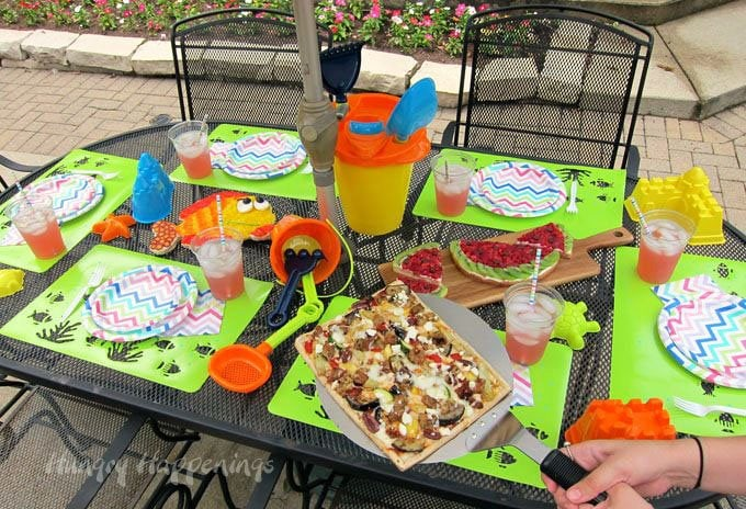 Decorate your pool party table with beach toys and serve festive pizzas for lunch. Recipes at HungryHappenings.com