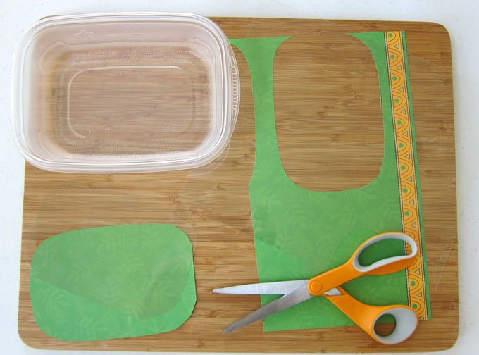 It's easy to decorate your plastic lunch containers with scrapbook paper and some acetate. It's a great way to dress up your kid's lunch.