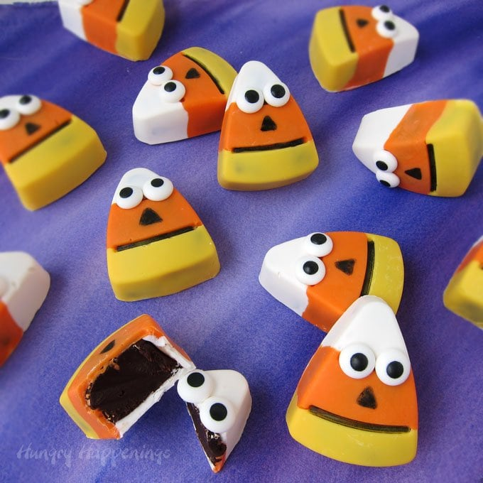 These cute Halloween treats are sure to appeal to adults and kids alike. Each decadent Chocolate Candy Corn Truffle has a yellow, orange, and white candy shell filled with luscious chocolate ganache, is decorated to look like a quirky little candy corn jack-o-lantern. Tutorial at HungryHappenings.com.