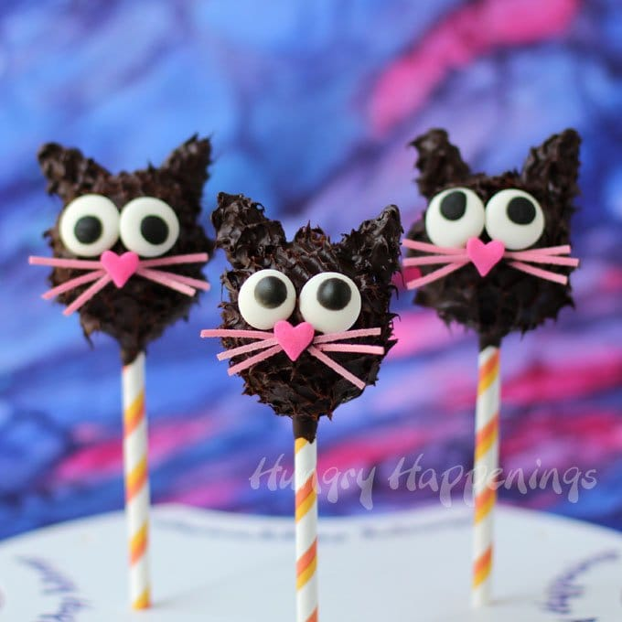 Wickedly cute Peanut Butter Fudge filled Black Cat Pops make the purr-fect Halloween treats. See how you can make them at home. The tutorial is at HungryHappenings.com.