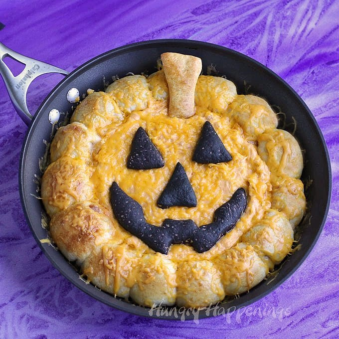 This Halloween, your party guests wont be able to resist breaking off pieces of cheddar cheese-filled pizza crust and scooping up some hot bubbly dip from this Skillet Buffalo Chicken Dip Jack-O-Lantern