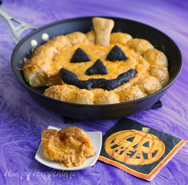 This Halloween instead of serving that plain bowl of buffalo chicken dip, impress your party guests with this dip baked in a skillet surrounded with gooey cheese-filled pizza puffs that can be broken off and used to scoop up the hot dip.