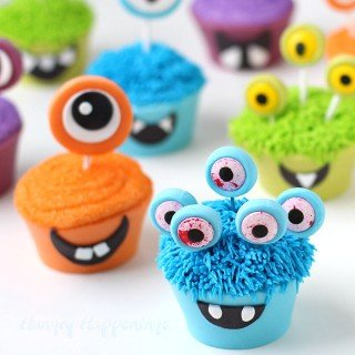 Serve these 100% edible Halloween cupcakes at your party this year and you wont have to deal with messy paper wrappers. These Cute Monster Cupcakes are made using edible cupcake wrappers created out of brightly colored modeling chocolate. Tutorial at HungryHappenings.com.