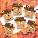 peanut butter and milk chocolate dipped pretzel sticks decorated with modeling chocolate to look like scarecrows