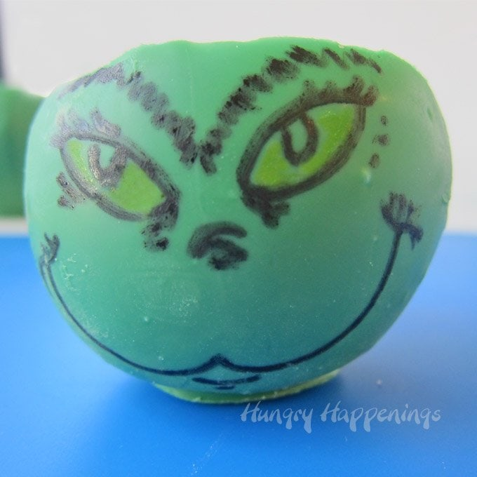 Hand draw faces onto green candy cups to make The Grinch for the holidays.