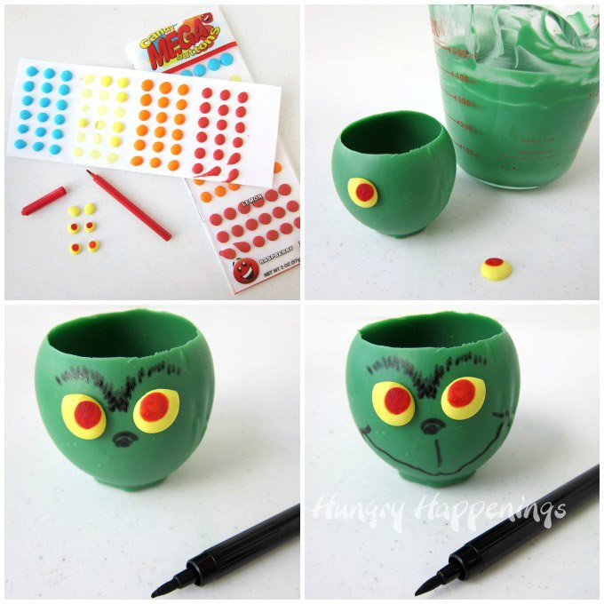 Decorate green candy cups with yellow candy button eyes then draw on the Grinch's nose, eyebrows, and mouth using a black food coloring marker.