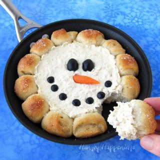 skillet dip snowman with bread puffs surrounding hot chicken dip decorated with black olives and a carrot nose