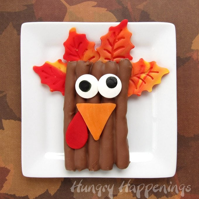Decorate chocolate pretzels to look like turkeys for Thanksgiving using colored modeling chocolate. It's easy and fun to do. See how at HungryHappenings.com.