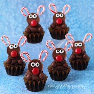 Decorate the ultimate chocolate cupcakes with peanut butter cup reindeer with candy cane antlers. See the tutorial at HungryHappenings.com.