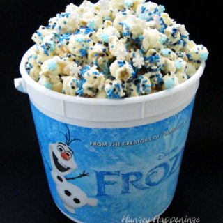 Snuggle up with your family and enjoy a movie night watching Disney's Frozen while munching on this fun snowflake sprinkle filled Frozen Popcorn.