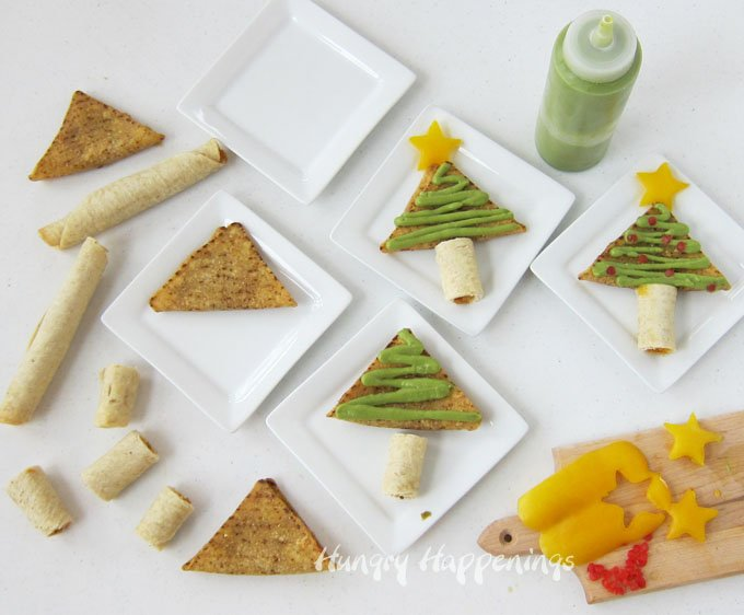 How to make Christmas Tree Snacks by decorating Taquitos and Nacho Bites with guacamole, peppers, and tomatoes.