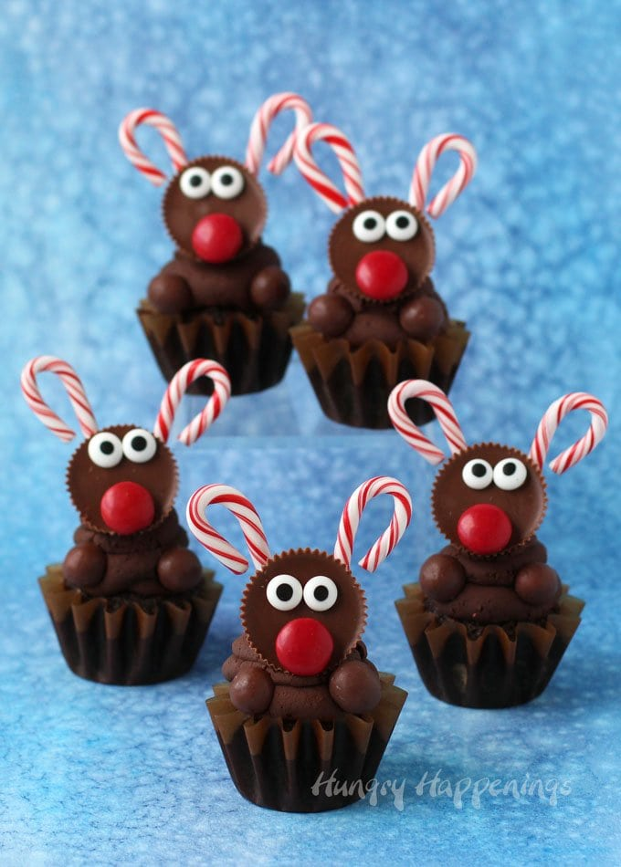 Decorate the ultimate chocolate reindeer cupcakes with peanut butter cup reindeer with bright red candy noses and candy cane antlers. See the tutorial at HungryHappenings.com.