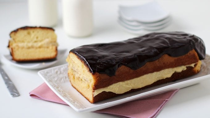 Serve a Chocolate Eclair Cake for breakfast or dessert. The luscious pastry cream sandwiched in between layers of cake topped with chocolate ganache makes a great treat any time of day. | HungryHappenings.com