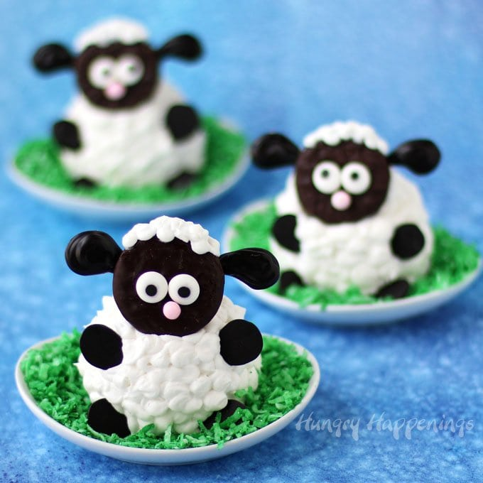 3 fluffy lamb cupcakes sitting a plates topped with green colored coconut grass set in front of a blue watercolor background
