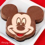Decadent chocolate Mickey Mouse Cheesecake. See how to decorate this fun cheesecake using colored plain cheesecake filling and chocolate cheesecake filling. You can find the tutorial at HungryHappenings.com.