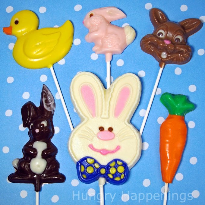 six Easter candy lollipops, including a duck, a pink bunny, a milk chocolate bunny, a dark chocolate bunny, a white chocolate bunny, and a carrot, are set on a bright blue and white polka dot background