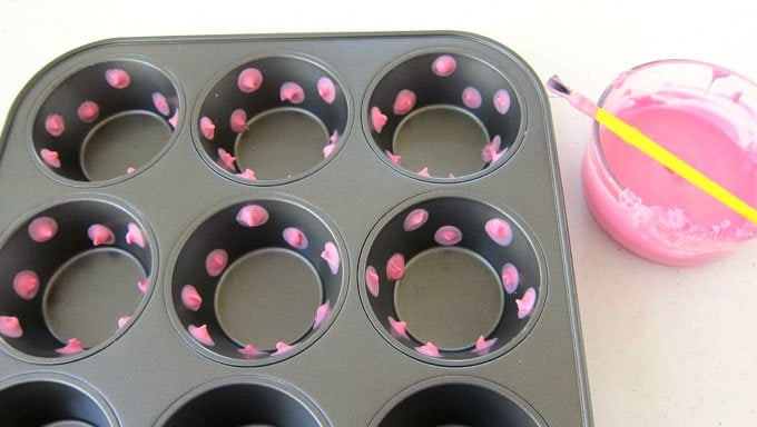 Paint pink polka dots using candy melts into a muffin tin to create Pink Polka Dot Candy Cups.